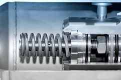 Part of the industrial mechanism. Blue toning. Part of the industrial mechanism with a metal spring. Blue toning stock photos