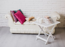 Part of interior with couch and decorative pillows, white wooden table with books on it. Interior details. White brick wall. Part of interior with couch and Royalty Free Stock Photography