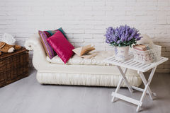Part of interior with couch and decorative pillows, white wooden table with books on it Royalty Free Stock Photo