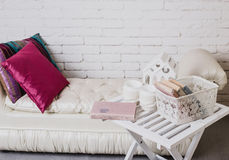 Part of interior with couch and decorative pillows, white wooden table with books on it. Interior details. White brick wall. Part of interior with couch and Royalty Free Stock Photo