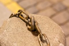 Part of an iron chain on a stone surface, urban texture. grunge metal industrial. Background Royalty Free Stock Images