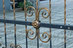 Part of the iron fence of steel brown and black rods with a forged pattern. On the street Stock Image