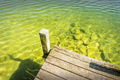 Part of a jetty over a lake of weathered wood with green-blue wa Royalty Free Stock Image