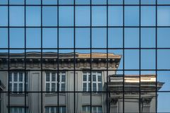 Part of the Jewish Historical Institute building in Warsaw, Poland, reflected in the glass facade of the modern building opposite. royalty free stock image