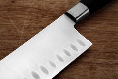 Part of the kitchen knife on an old cutting board Stock Photography