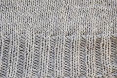 Part of a knit project, sweaters close-up, top view. Classic loops made of gray threads of Italian wool yarn. The concept of stock photo