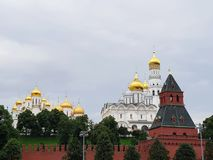Kremlin Churches. Part of Kremlin wall and white churches with golden domes behind it Stock Photo