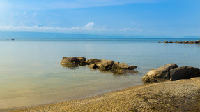 Part of lake Leman coast. With the small gravel beach and many rocks in water. Lausanne Switzerland Stock Image