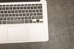 Part of the laptop keyboard on a black wooden table. Workplace. Top view Royalty Free Stock Photo