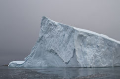 Part of a large iceberg in Antarctic waters on a cloudy autumn d Stock Image