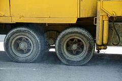 Part of a large yellow truck with two wheels on the asphalt. Part of a large yellow truck with two black wheels on the asphalt stock photos