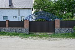 Part of a long brown fence and gate of iron and stone in the street near the road from sand stock image