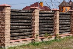 Part of a long brown fence made of bricks and wooden boards on a rural street stock image