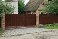 Part of a long metallic brown fence and a large gate outside in the grass royalty free stock photos