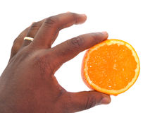 PART OF MAGIC. A magician holding a slice of orange exercising a practice intended to intervene in a supernatural way to impress the observers Stock Photos