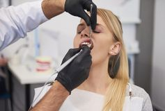 Stomatologist giving woman anesthesia in dentist`s clinic. Part of male stomatologist giving women anesthesia in dentist`s clinic stock images