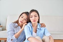 Part malheureuse de jeune femme au sujet de son probl?me ? la maison avec son ami photographie stock