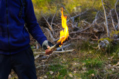 Part of a man and hand with torch  flame in wild nature background. Royalty Free Stock Image