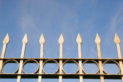 Part of the metal fence. Part of a metal fence with spikes against a blue sky. Photo closeup Stock Photos