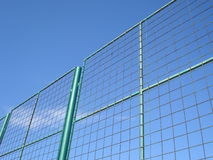 Part of metal grid tall fence, against blue sky Royalty Free Stock Images