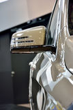 Part and mirror of a luxury sedan. Part of a luxury sedan in gray color, rear view mirror and car body Stock Images