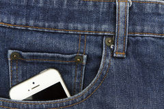 Part of mobile white cellphone in the front pocket of blue denim Royalty Free Stock Photos