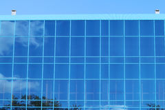 Part of modern building with blue windows with reflection Royalty Free Stock Photo