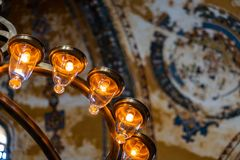 Part of a modern electric chandelier with warm light in front of a blurred painted ceiling in a historic building. royalty free stock photo