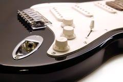 Part of modern electric six string guitar black color closeup. Part of modern electric six string guitar black color with glossy finish with empty metal jack royalty free stock image