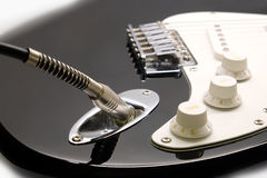 Part of modern electric six string guitar black color closeup. Part of modern electric six string guitar black color with glossy finish with jack in socket stock photography