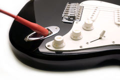 Part of modern electric six string guitar black color closeup. Part of modern electric six string guitar black color with glossy finish with red cord in socket Stock Photos