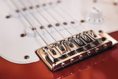 Part of modern electric six string guitar red color with glossy finish, pickups and control knobs  on wooden background cl. Ose up view Stock Photo