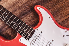Part of modern electric six string guitar red color with glossy finish, pickups and control knobs on wooden background cl royalty free stock image