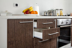 Part of modern kitchen with electric stove oven, drawers, handle. And fruits Stock Photography