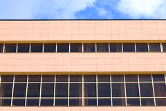 Part of modern new brown building with windows and blue sky Royalty Free Stock Photo