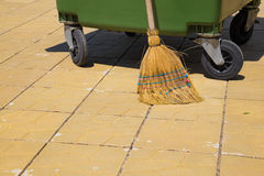 Part of a modern plastic bin with an old straw broom Royalty Free Stock Images