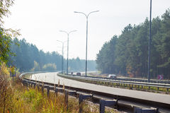 Part of the motorway with forest on both sides autumn Royalty Free Stock Photography