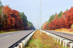 Part of the motorway with forest on both sides autumn Royalty Free Stock Image