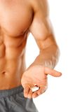 Part of muscular man torso with hand full of pills Stock Images