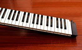 Part of the music keyboard. On a wooden background royalty free stock image