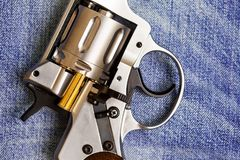 Nagan revolver with collet. Part of Nagan revolver with collet on blue jeans background, close-up Stock Images