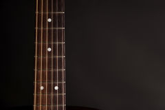 Part of the neck, wooden acoustic guitar, on the left side of the frame, on a black isolated background Royalty Free Stock Photography