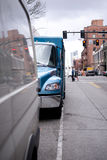 Part of new blue semi truck with box trailer on busy city street royalty free stock image