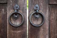 Part of oak doors with handles in the form of rings. Part of oak doors with wrought iron handles in the form of rings royalty free stock images