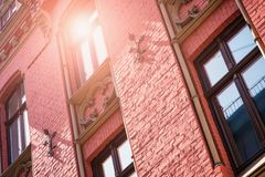 Free Part Of The Facade Of A Red Historic Building Illuminated, Reflecting Off Window Panes, In The Old Riga Town . Series - Old Riga T Stock Photography - 157200102