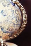 Part of old antique globe and longitude degrees. Indoors colored closeup vertical image on dark background Royalty Free Stock Photo