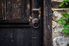 Part of old brown wooden door. With rusted iron ring Royalty Free Stock Photos