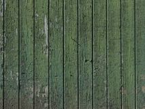 Part of old green painted barn door with vertical planks. Part of old worn down grungy green painted barn door with vertical planks Stock Photo