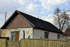 Part of the old house behind a green wooden fence. Old private house in the yard Stock Images