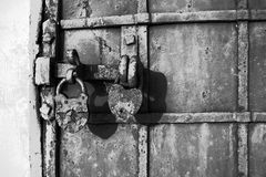 Part of an old metal gate with a latch and two locks of an old historic building. Black and white, retro, vintage royalty free stock photography